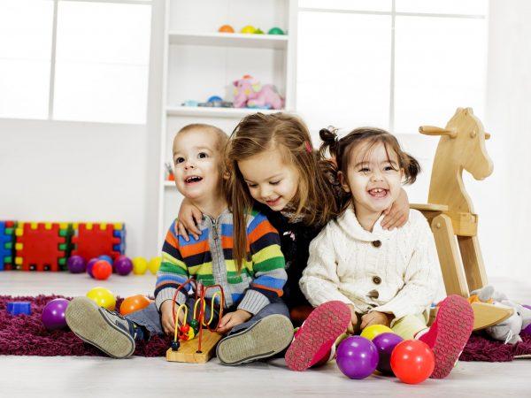 Na foto três crianças brincando.
