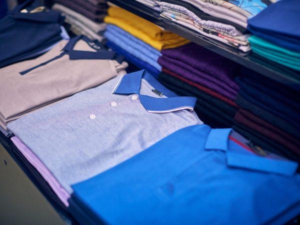 Pilhas de camisas polo dobradas sobre bancada de loja