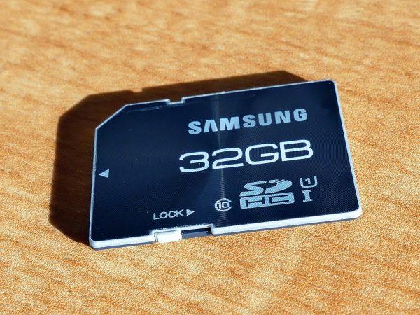 Imagem mostra um cartão de memória 32GB sobre uma mesa.