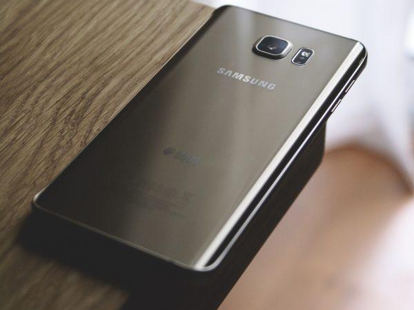 Mão de mulher tirando foto com um celular da Samsung.