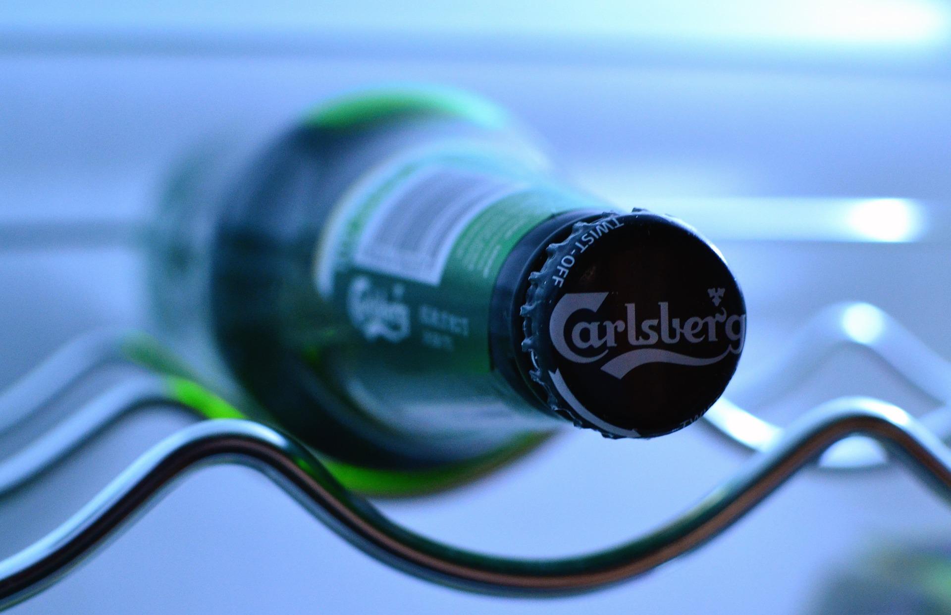 Imagem mostra um close na tampa de uma garrafa de cerveja, que está deitada numa prateleira de uma cervejeira .