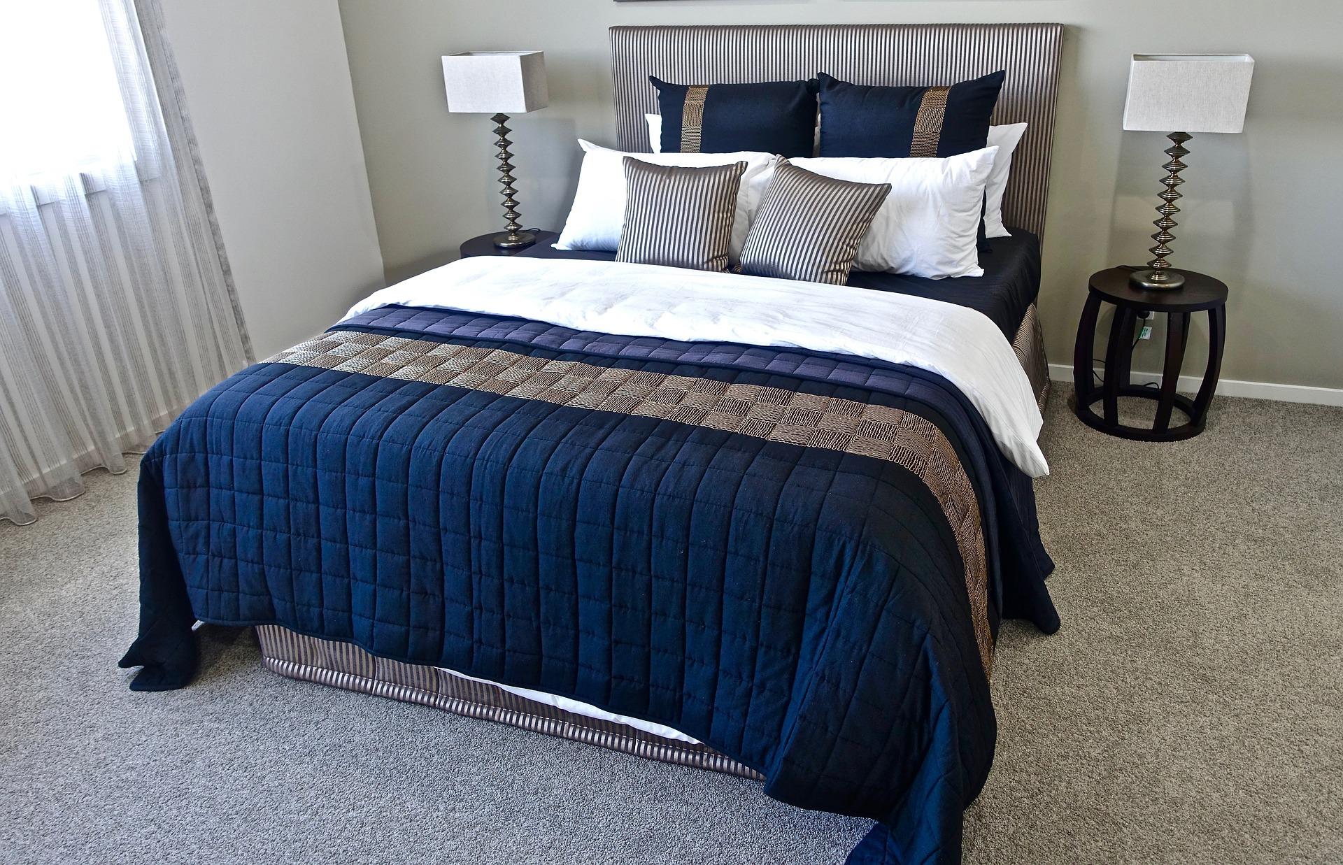 Na foto uma cama de casal com roupa de cama azul e cinza entre dois abajures.