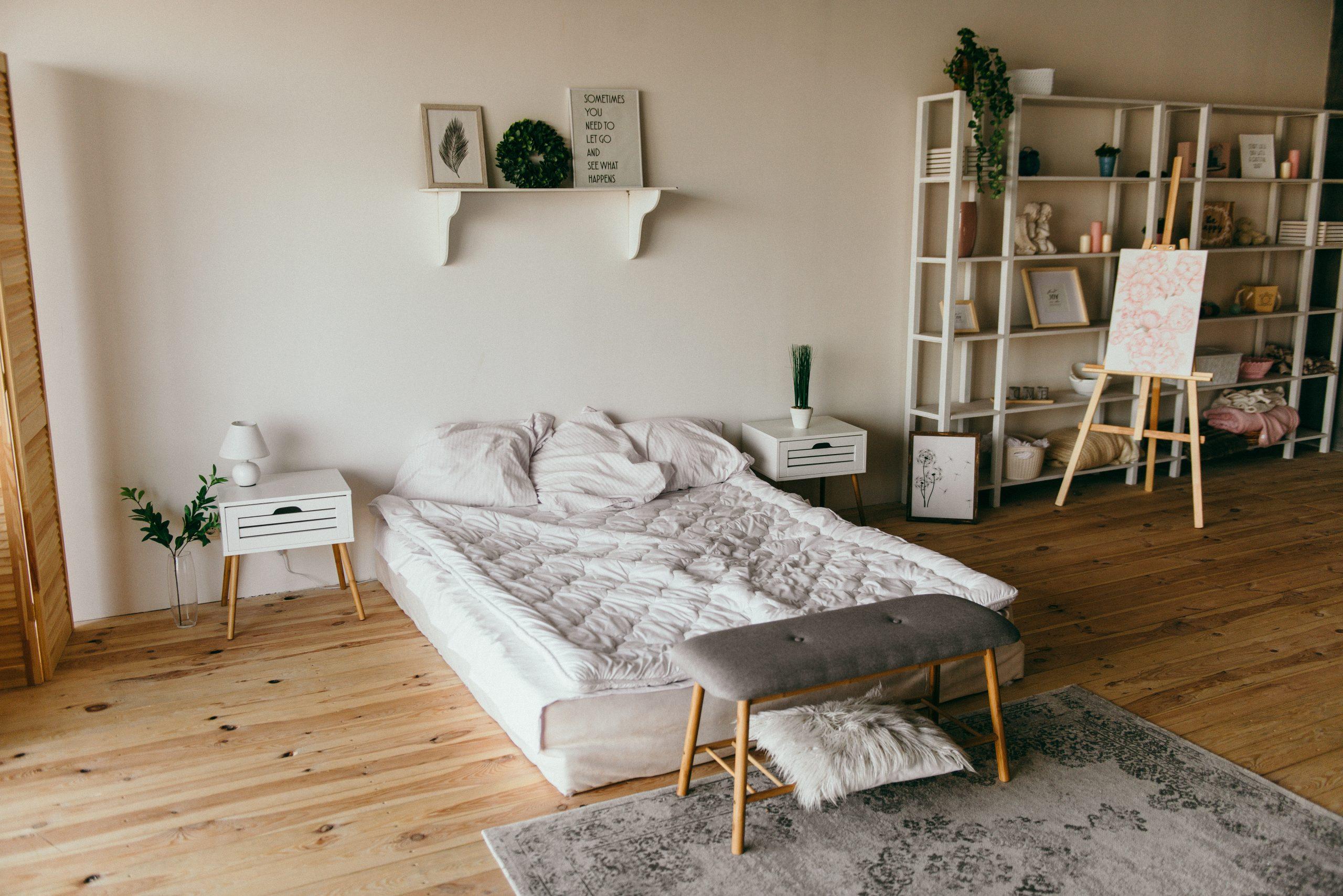 Imagem mostra uma sala de piso de taco de madeira, amplo espaço e iluminada, com foco num colchão diretamente no chão, com roupa de cama levemente bagunçada, e três travesseiros apoiados sobre ele.