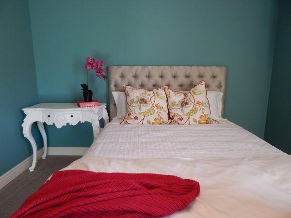Imagem de quarto com cama de solteiro e criado com flor
