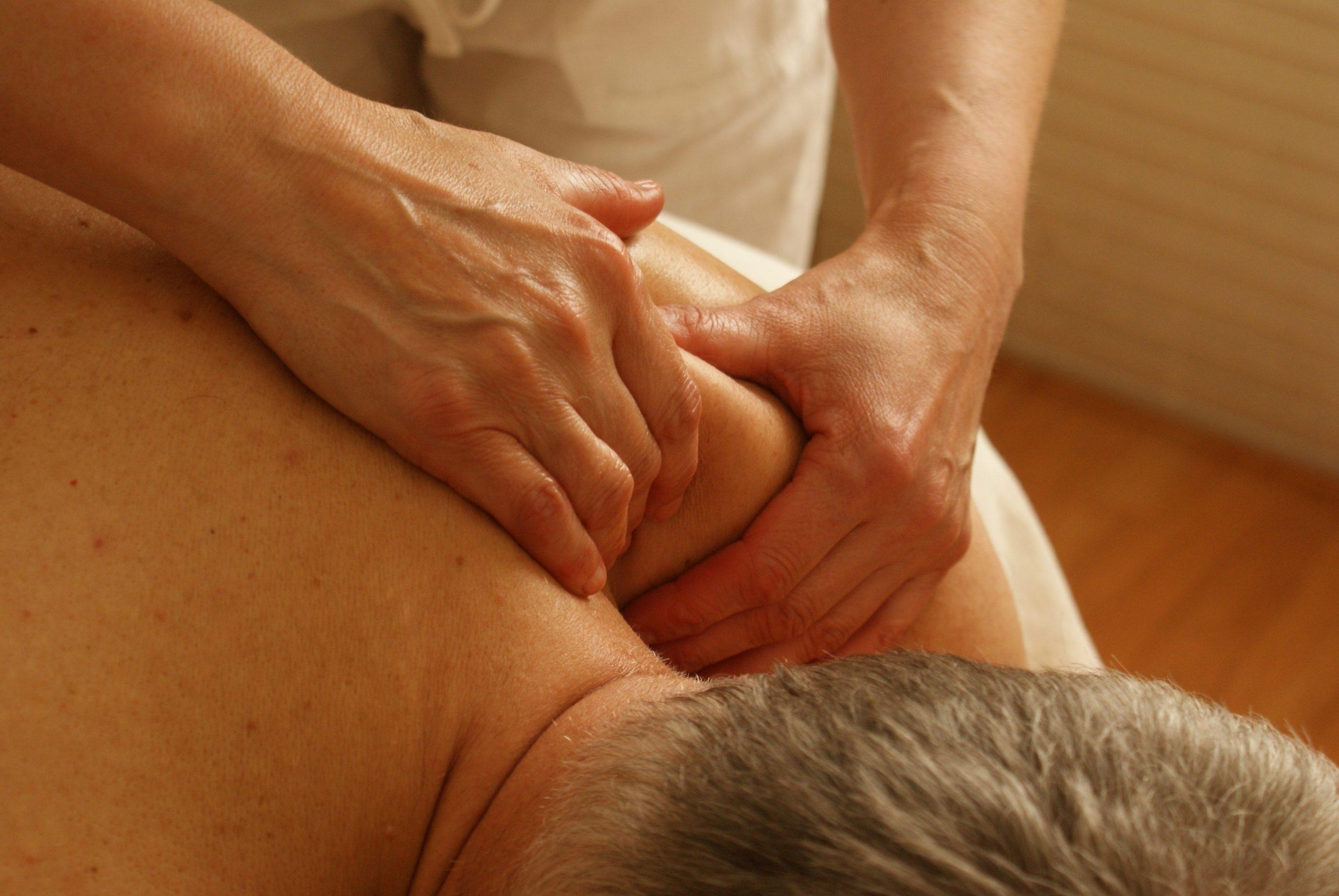 Foto de um home deitado de bruços, com mãos femininas massageando seu ombro.