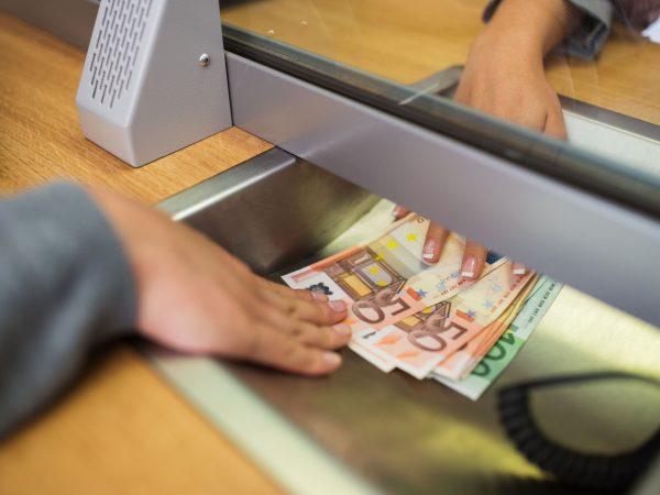 Mulher pegando dinheiro no banco.