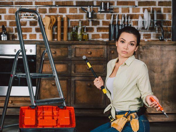 Imagem mostra uma mulher segurando ferramentas ao lado de uma escada 3 degraus.