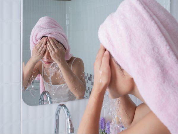 Imagem de uma mulher de frente para o espelho jogando água no rosto.