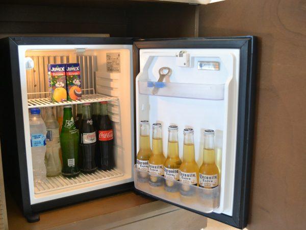 Frigobar aberto com bebidas.