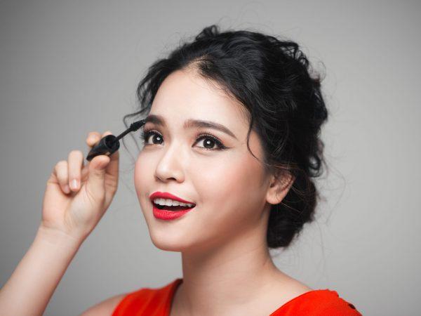 Na foto uma mulher aplicando um produto na sua sobrancelha.