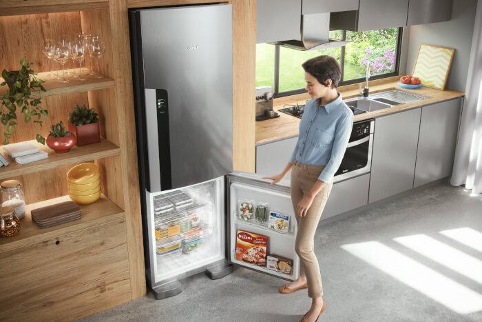 Imagem de mulher observando o interior de uma geladeira Consul inox