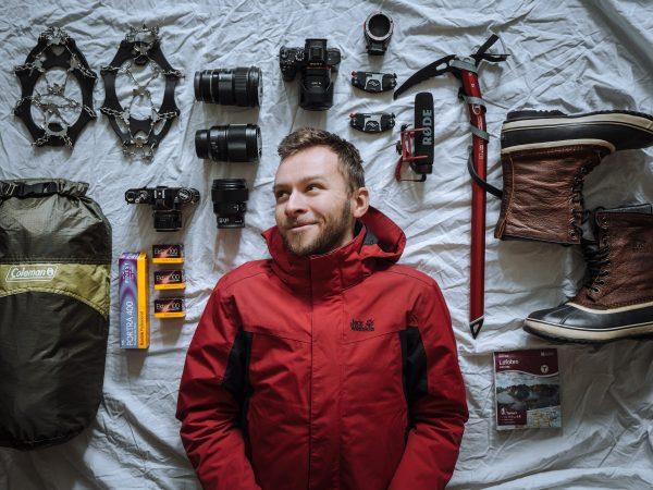 Rapaz veste jaqueta Anorak deitado em meio a equipamentos para montanhismo