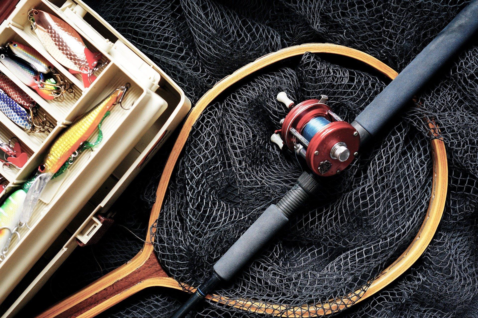 Imagem mostra diversos equipamentos de pesca, como vara, carretilha e iscas.