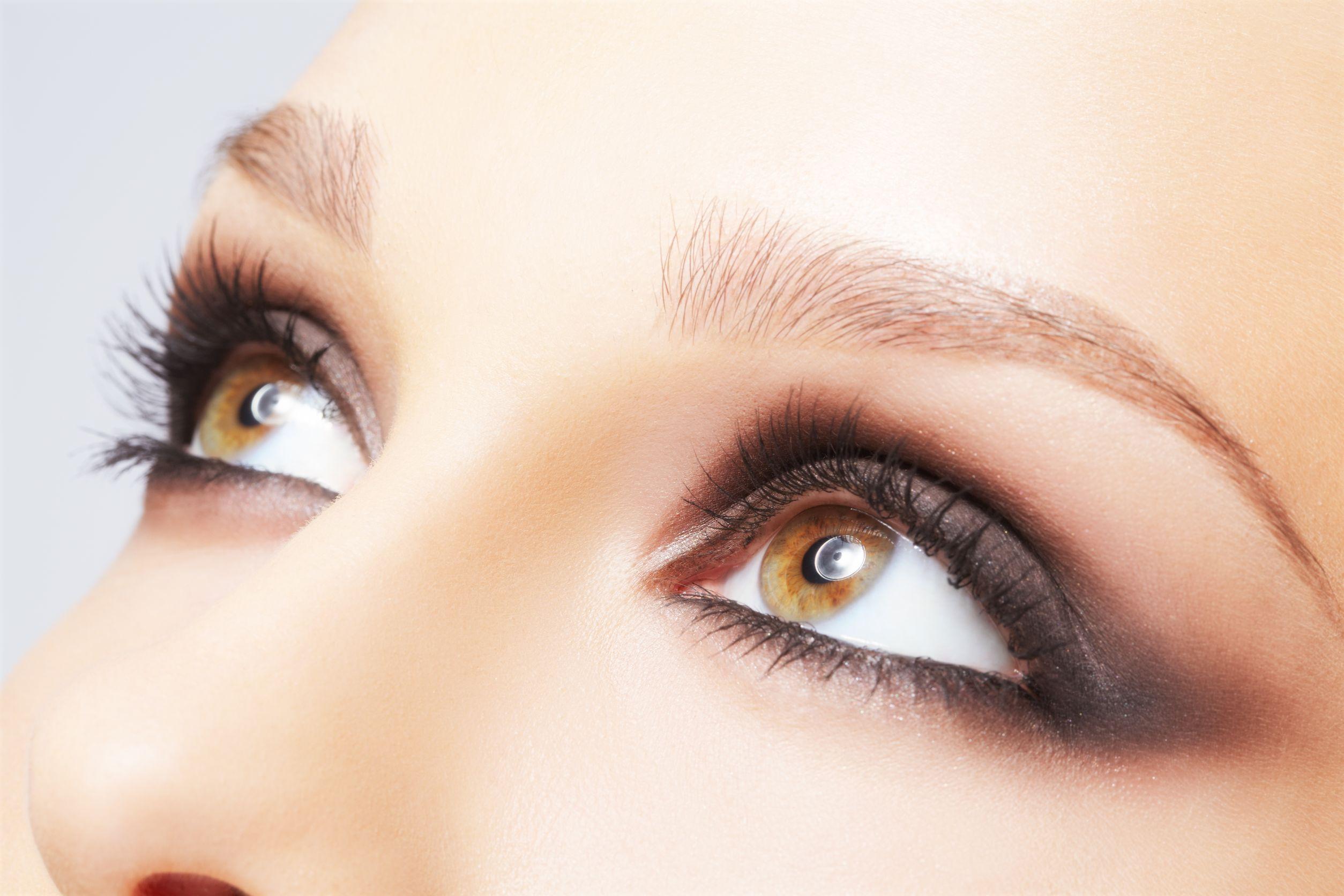 Foto focada nos olhos castanhos de uma mulher, que usa lápis de olho, sombra escura e máscara de cílios.