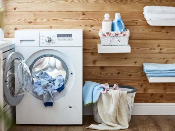 Na foto uma máquina de lavar com roupas dentro de uma lavanderia.