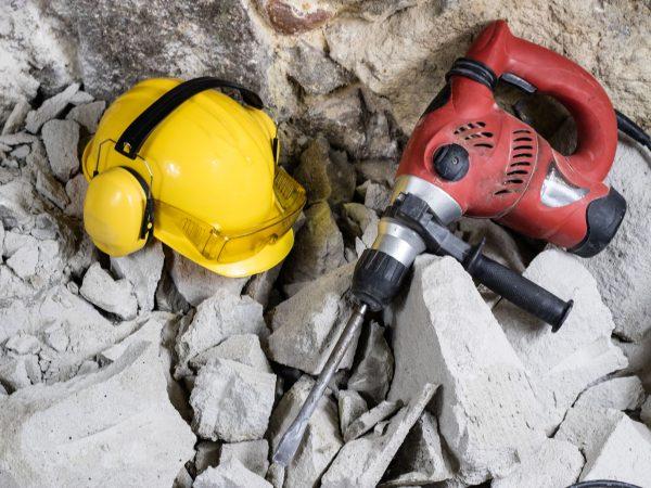 Imagem mostra um martelete ao lado de um capacete de proteção sobre pedaços de concreto.