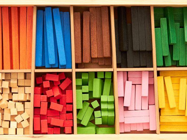 Na foto uma caixa com diversas peças de madeira coloridas.