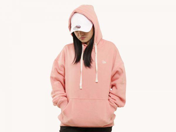 Uma mulher, com as duas mãos bolso, está vestindo um moletom New Era rosa. Ela está com o capuz sobre sua cabeça e de seu boné branco.