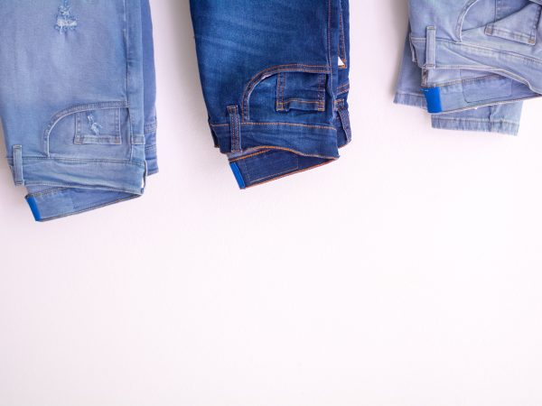 Foto que mostra parte de três calças jeans dobradas, em um fundo branco.