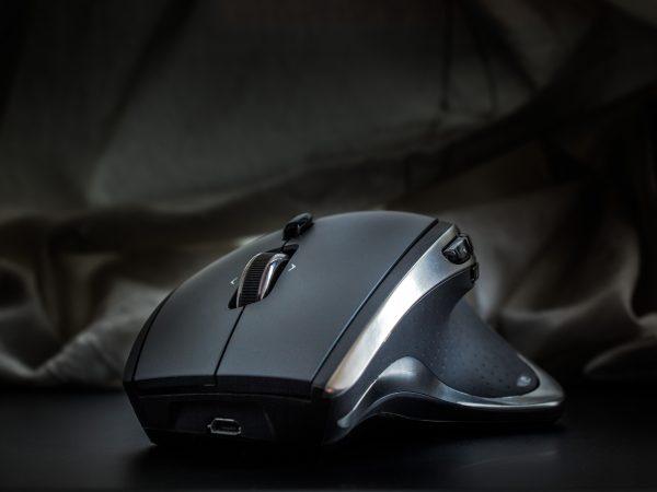 Imagem mostra um plano detalhe da parte frontal de um mouse sem fio, com um formato ergonômico.