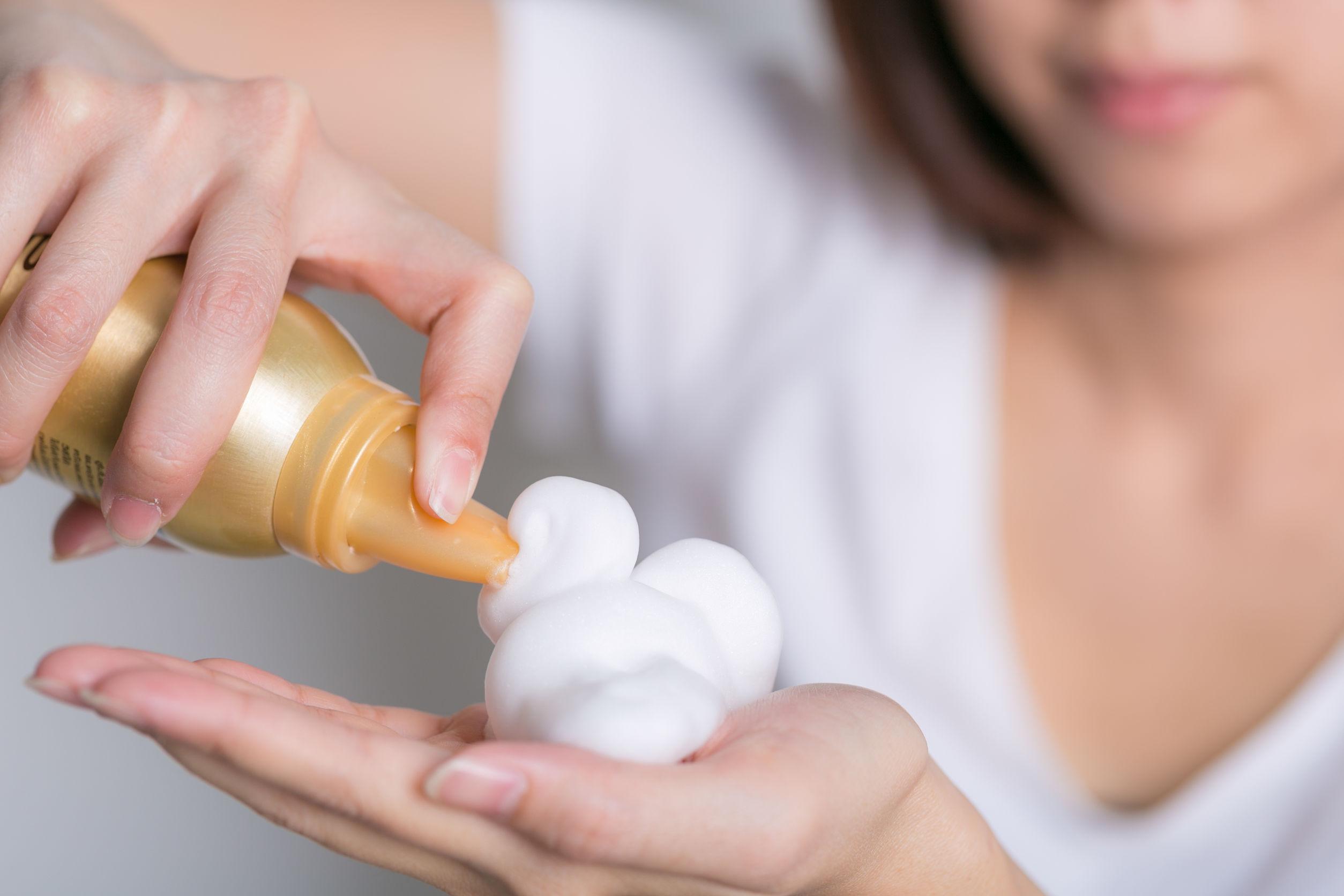 Imagem de mulher colocando mousse para cabelo em uma das mãos