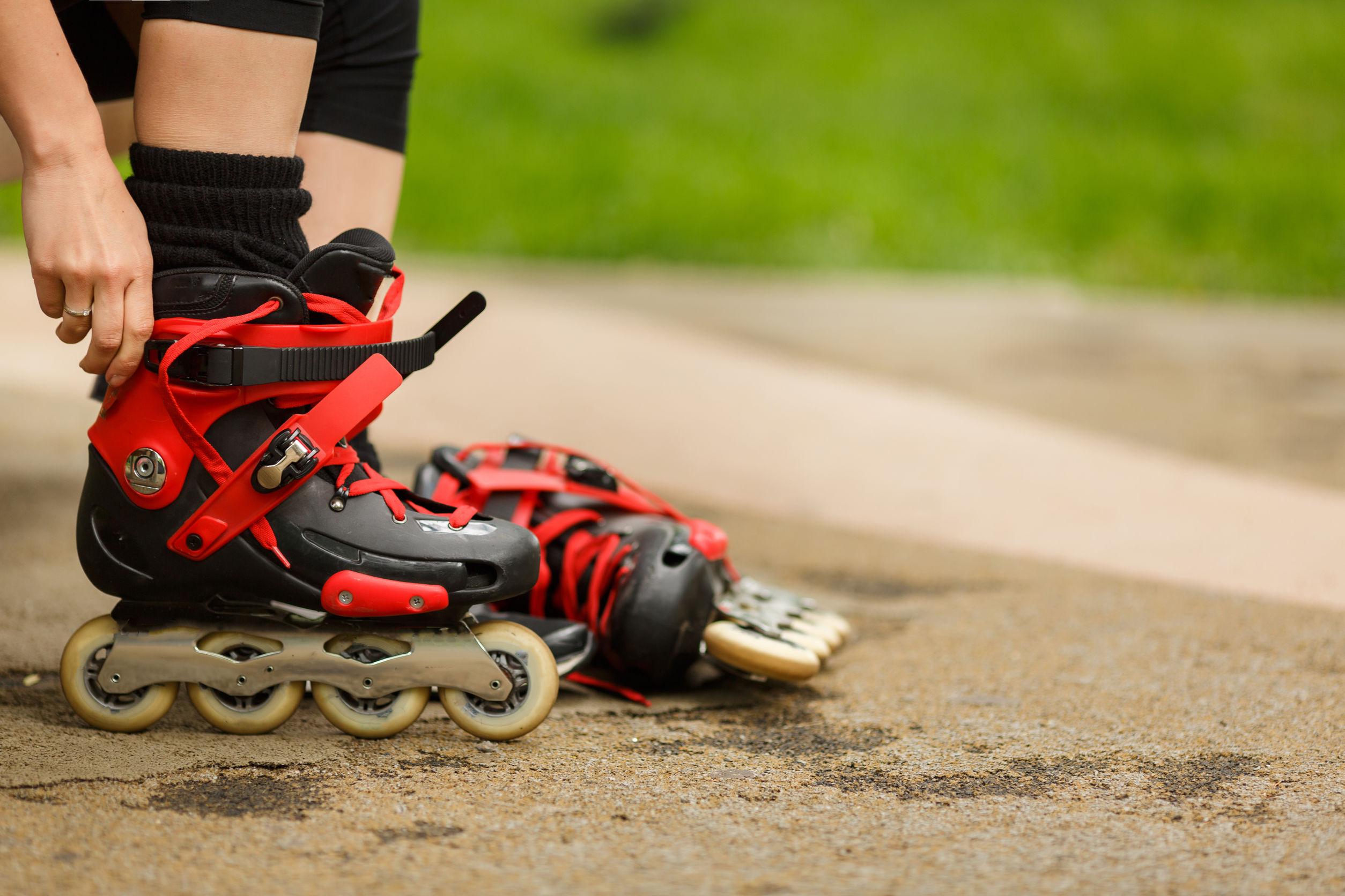 Imagem mostra uma mão de uma pessoa ajustando um patins no seu pé, apoiado verticalmente sobre suas quatro rodas em linha, com o outro pé do patins deitado ao seu lado