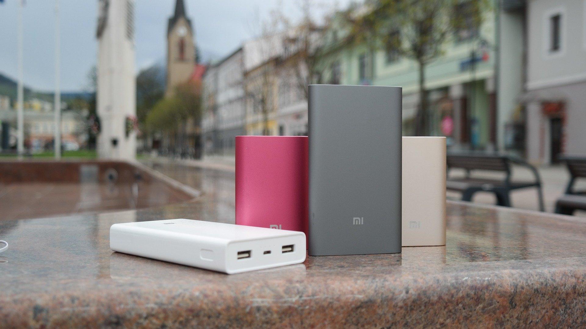 Imagem mostra quatro power banks da Xiaomi, de tamanhos e cores diferentes, apoiados sobre uma mureta de mármore.