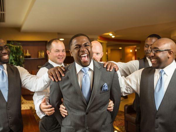 Imagem mostra um noivo rindo, rodeado de seus padrinhos, que apoiam uma mão cada em cima dele.