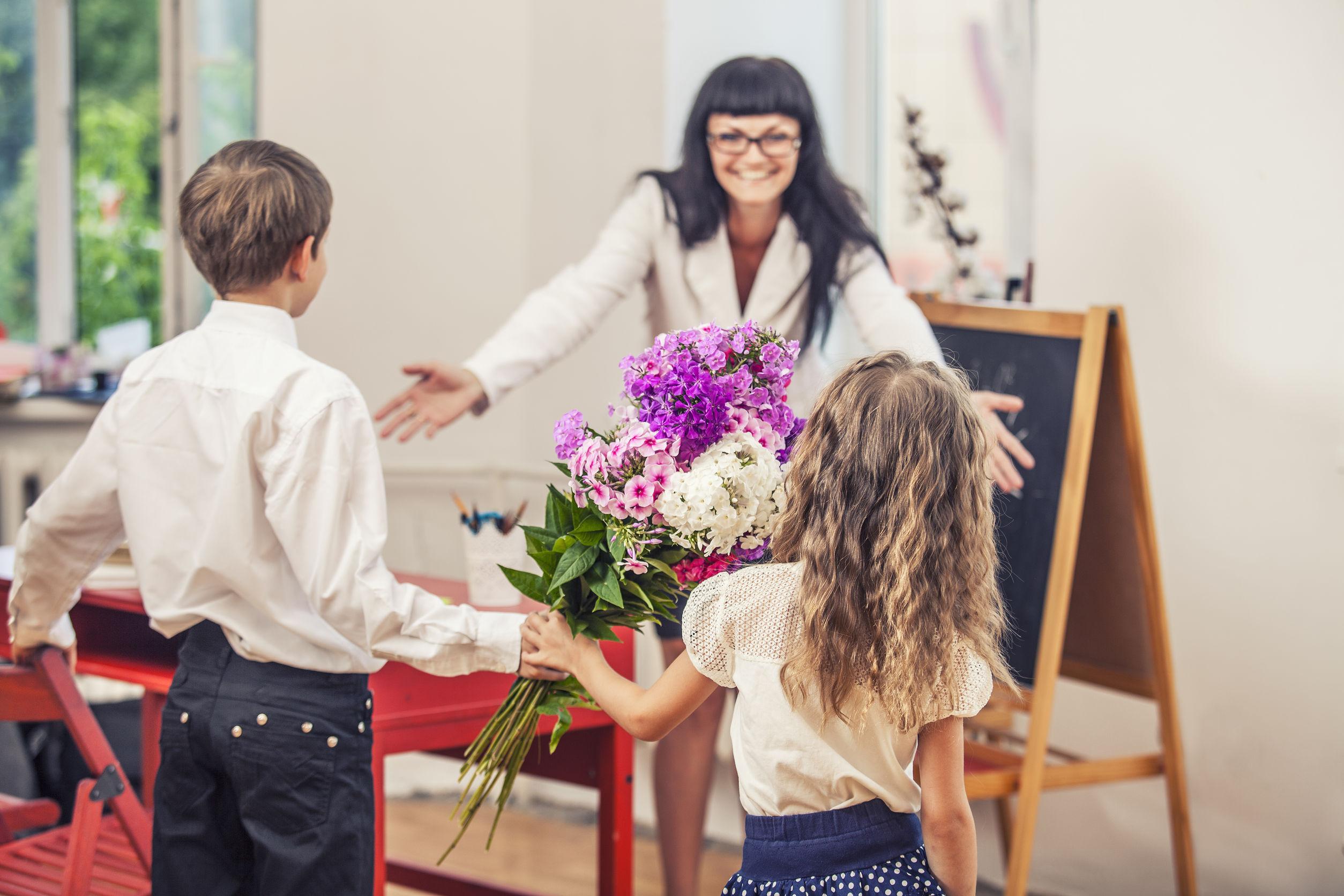Na foto uma professora de braços abertos e dois alunos indo ao seu encontro segurando flores.