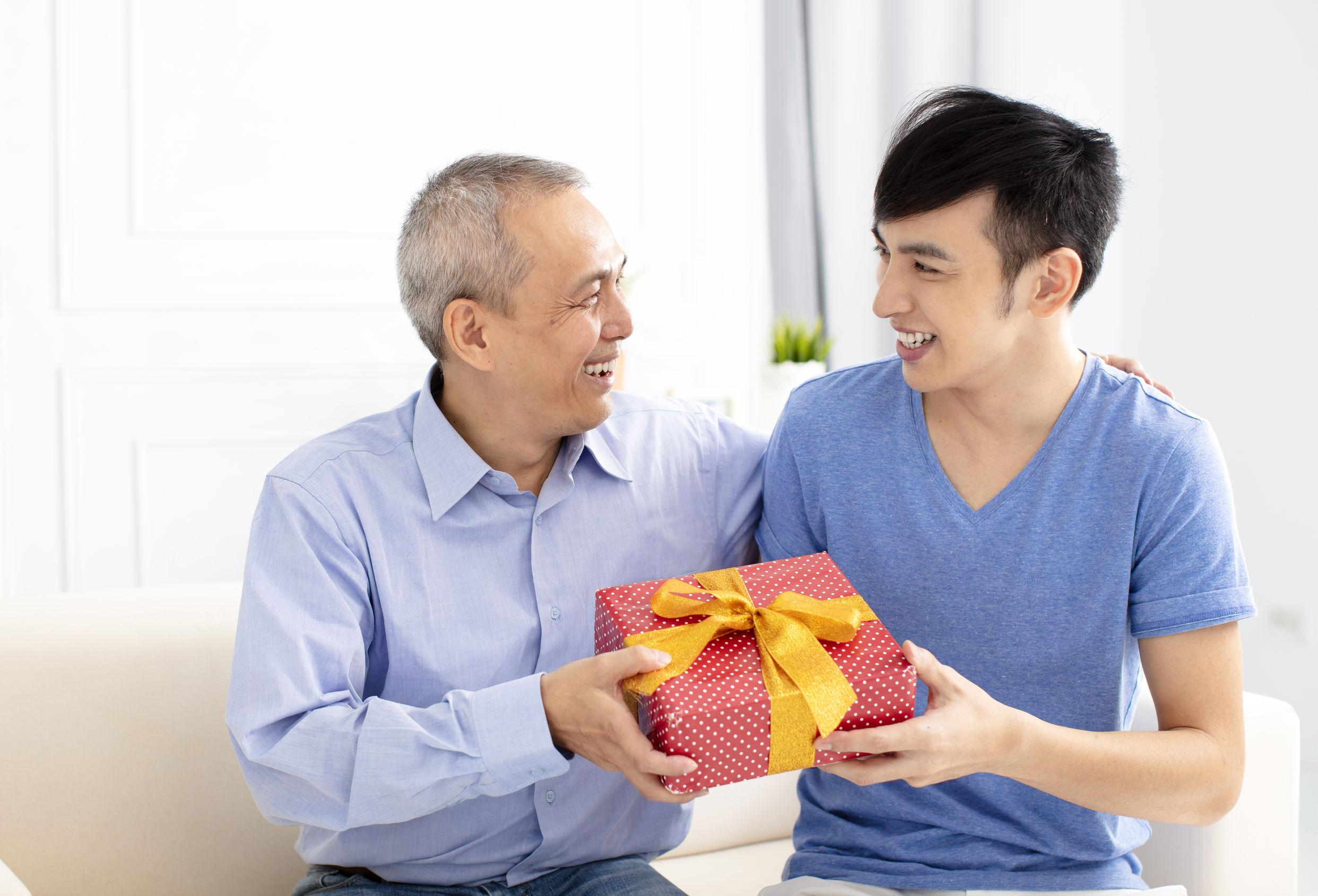 Na foto um homem entregando um presente para outro.