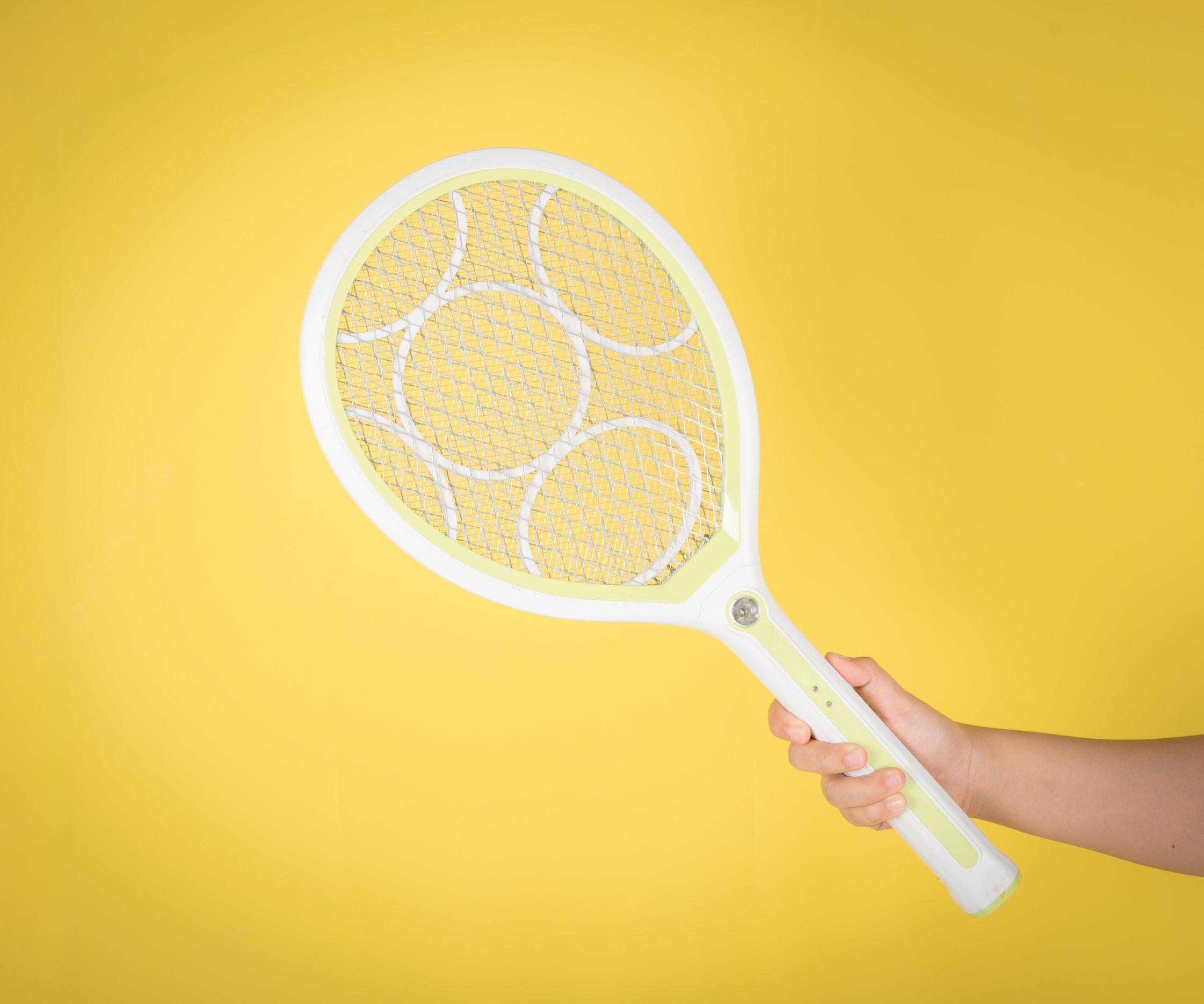 Na foto uma mão segurando uma raquete elétrica em um fundo amarelo.