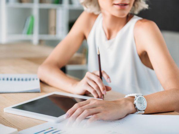 Na foto uma mulher sentada atrás de uma mesa com um tablet na sua frente.