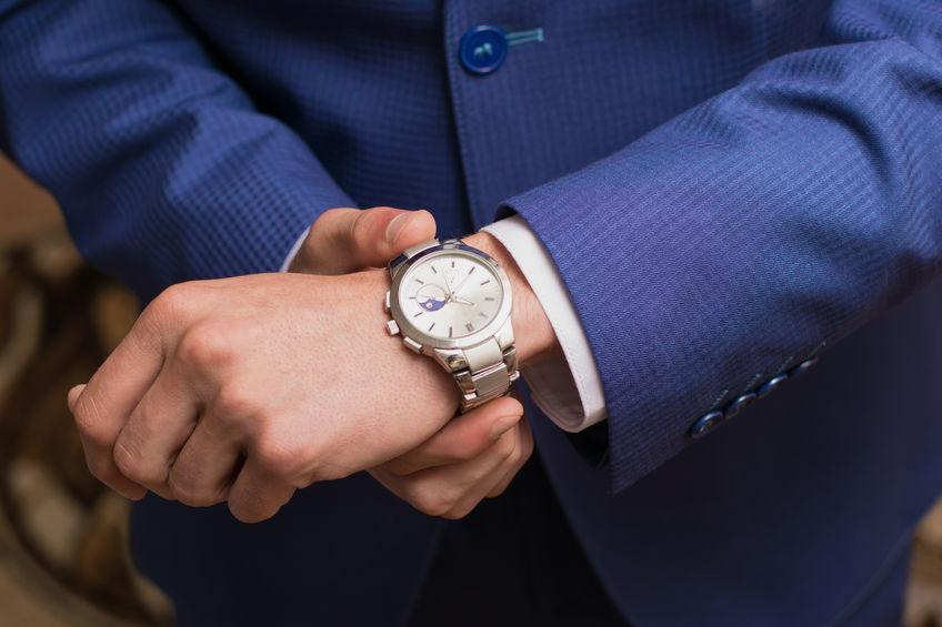 Um homem ajeita a camisa social com seu braço esquerdo, que traz em seu pulso um relógio Armani.