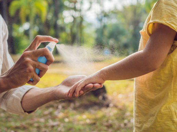 Imagem mostra um adulto espirrando repelente no braço de uma criança.