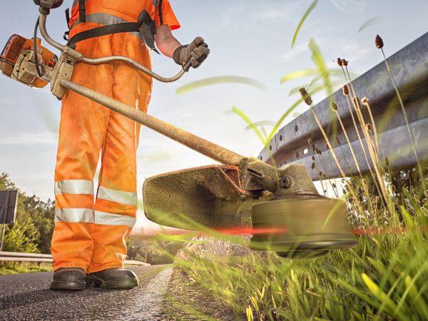 Imagem mostra um trabalhador usando uma roçadeira lateral.