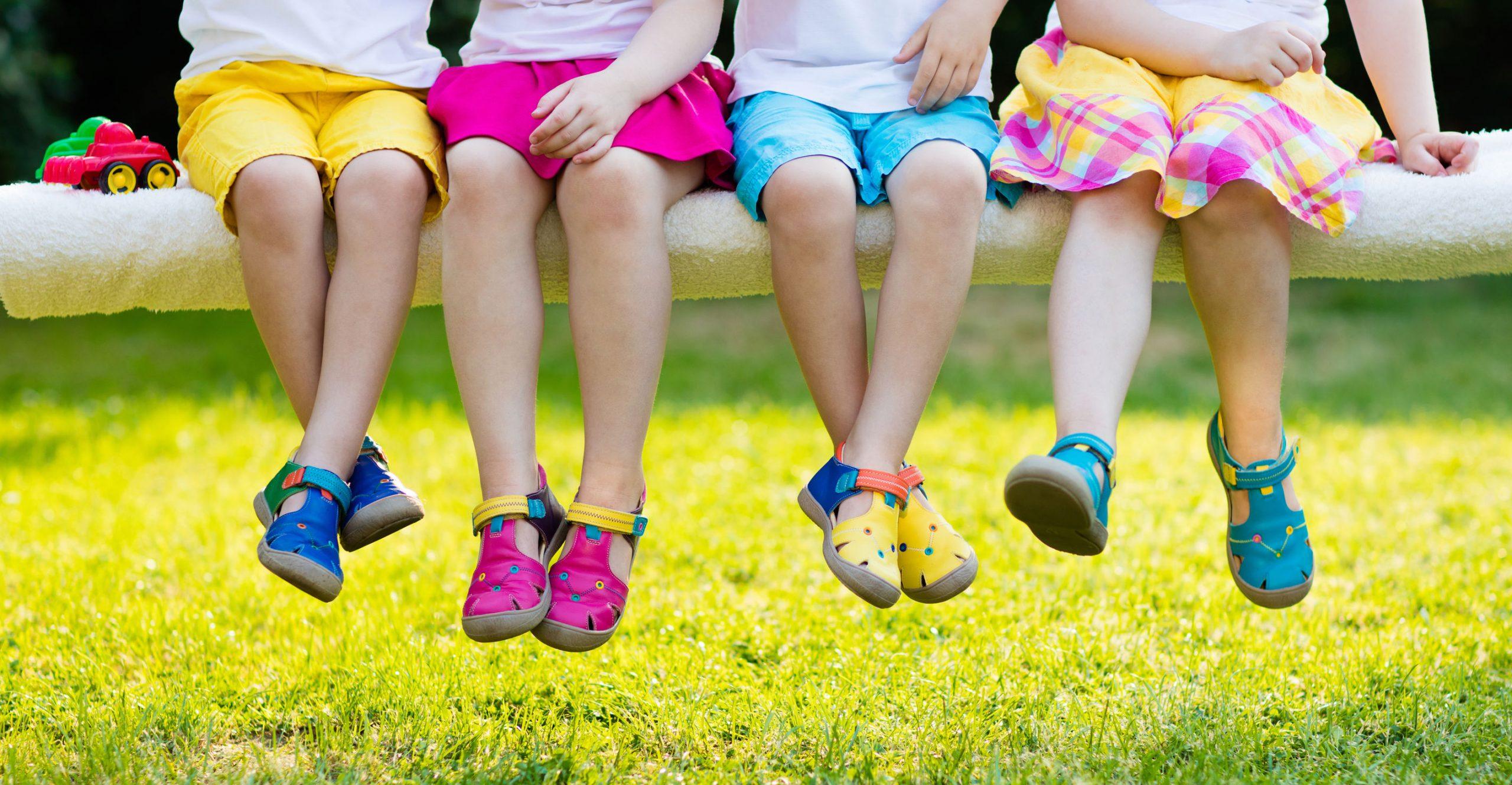Duas meninas posam para foto segurando sandálias
