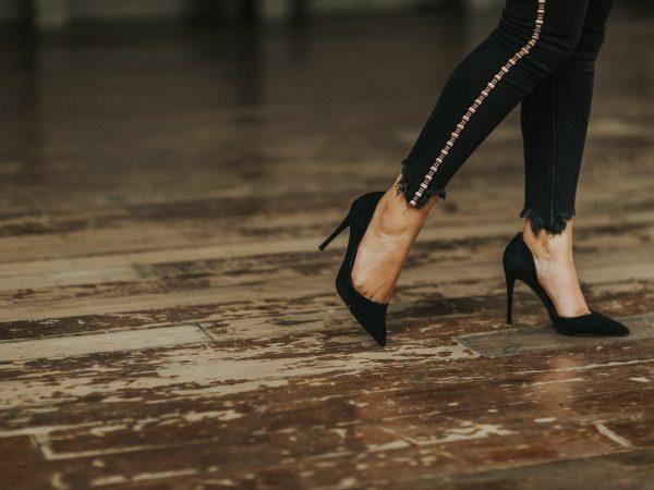 Foto que mostra do joelho pra baixo de uma mulher, que veste calça jeans skinny preta e scarpin preto. O chão é de madeira e está gasto.
