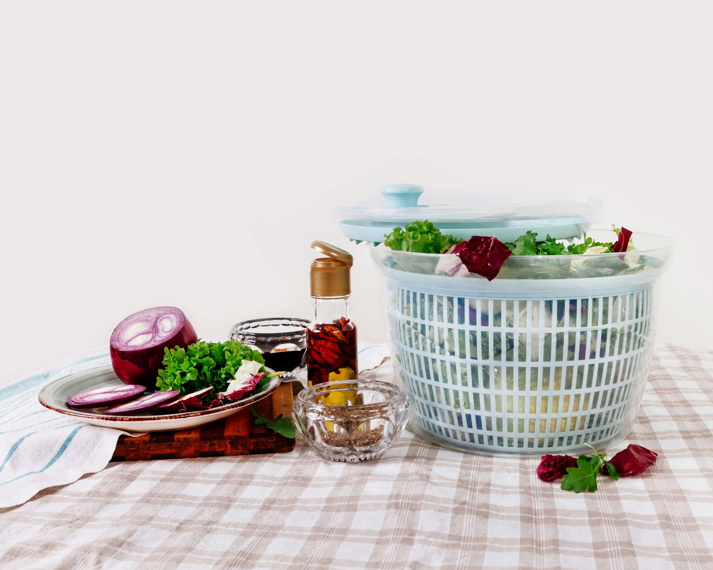 Na foto um secador de salada em uma mesa com legumes e temperos.