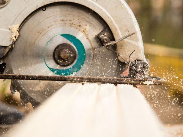 Imagem mostra uma serra circular cortando um pedaço de madeira.