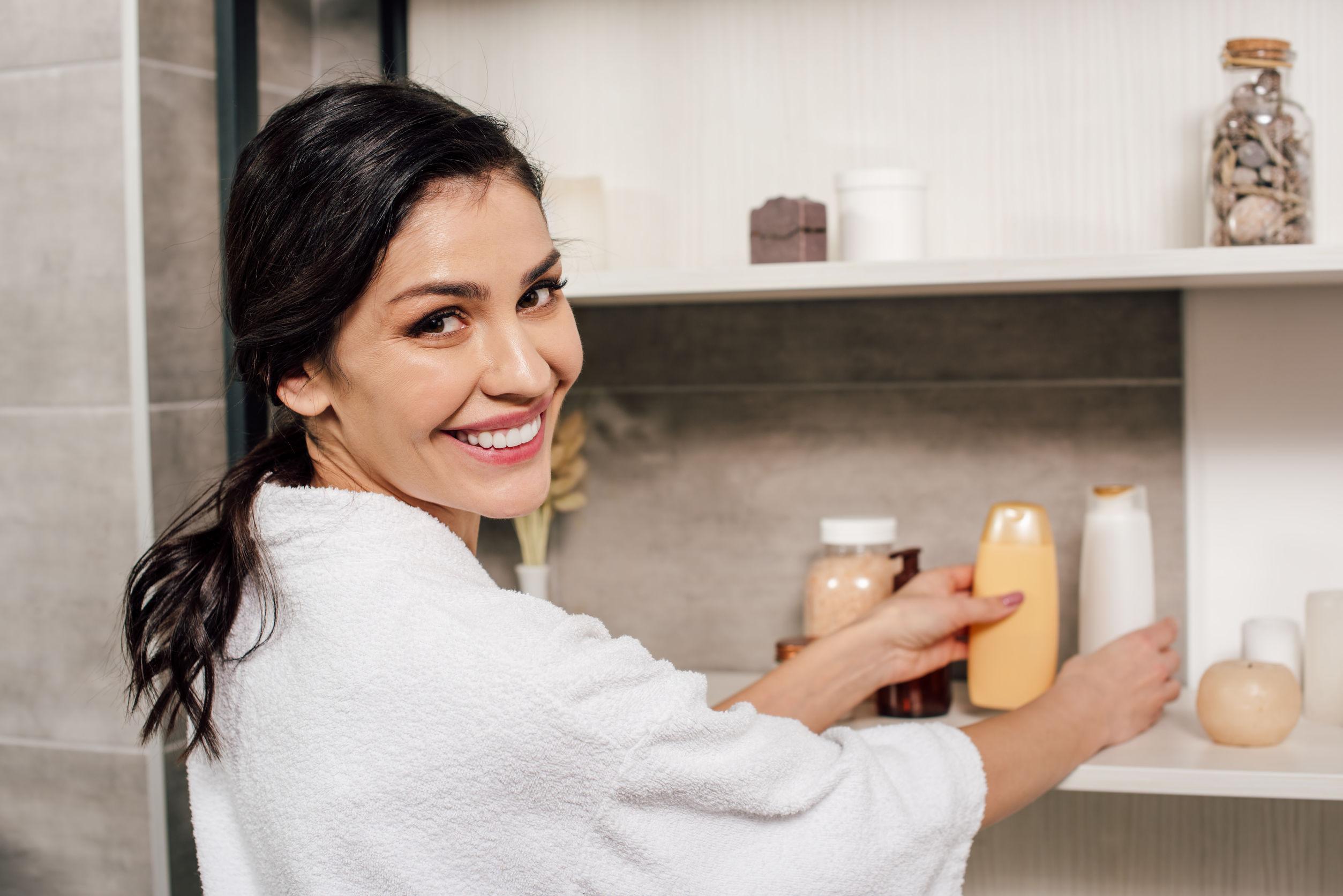 Imagem de uma mulher organizando cosméticos em uma prateleira.
