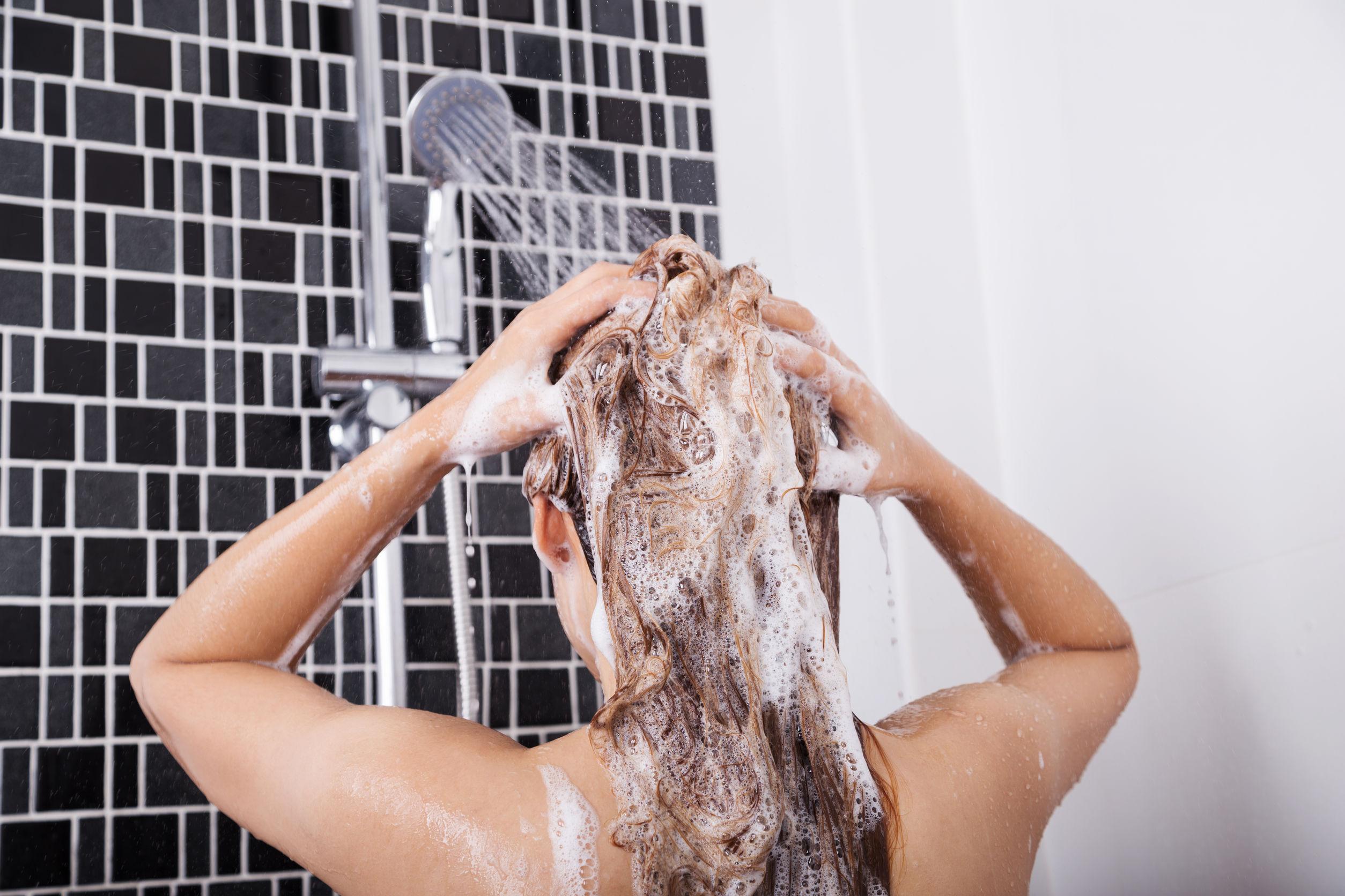 Mulher de cabelos escuros lavando os cabelos no chuveiro com parede branca e shampoos ao fundo