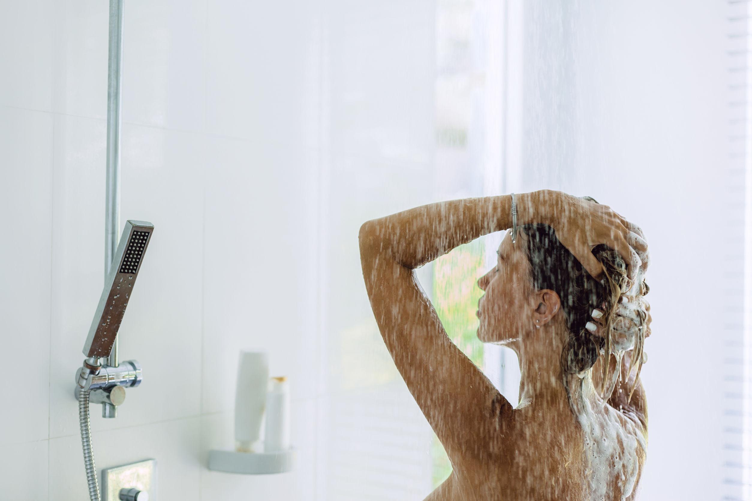 Foto de uma mulher tomando banho e lavando o cabelo em um banheiro com parede branca.