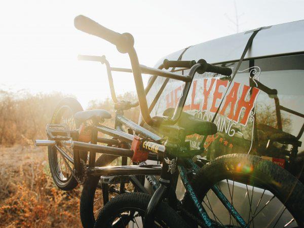 Imagem mostra duas bicicletas amarradas na parte traseira de um carro, iluminado pelo sol nascente.