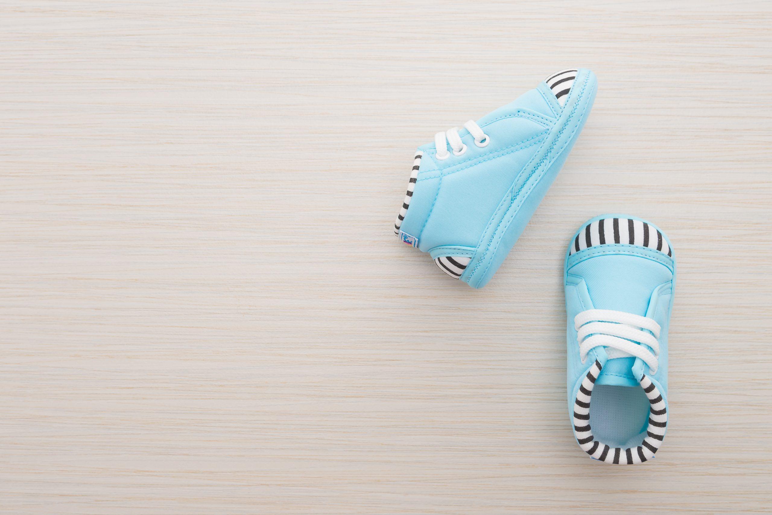 Dois sapatinhos de bebê na cor azul sob uma superfície de madeira clara.