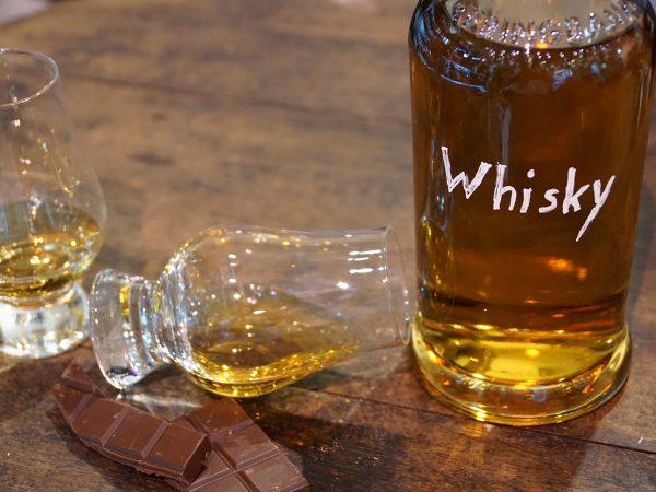 imagem de dois cálices com líquido e uma garrafa com uísque.