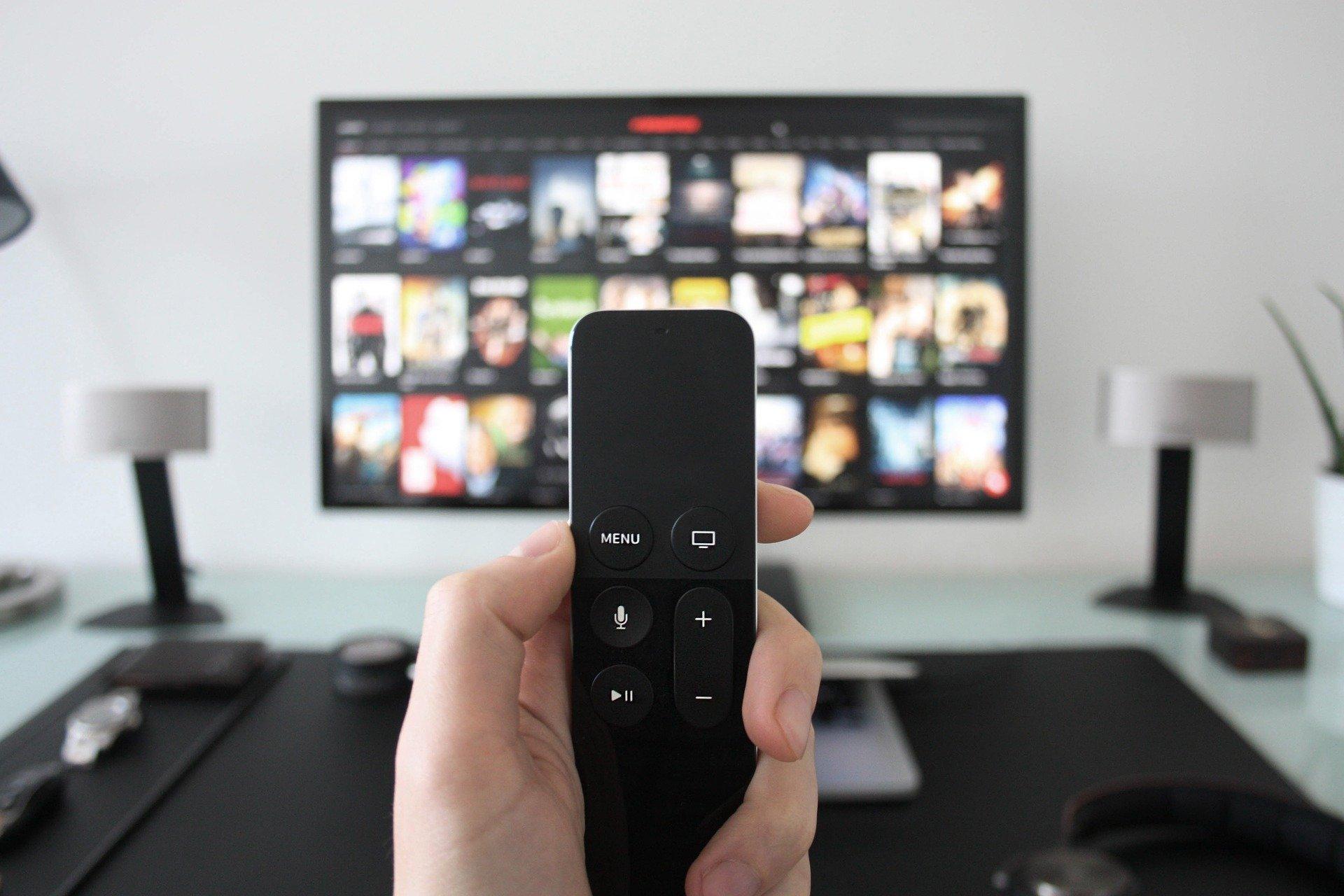 Imagem de pessoa segurando um controle remoto em frente a uma TV