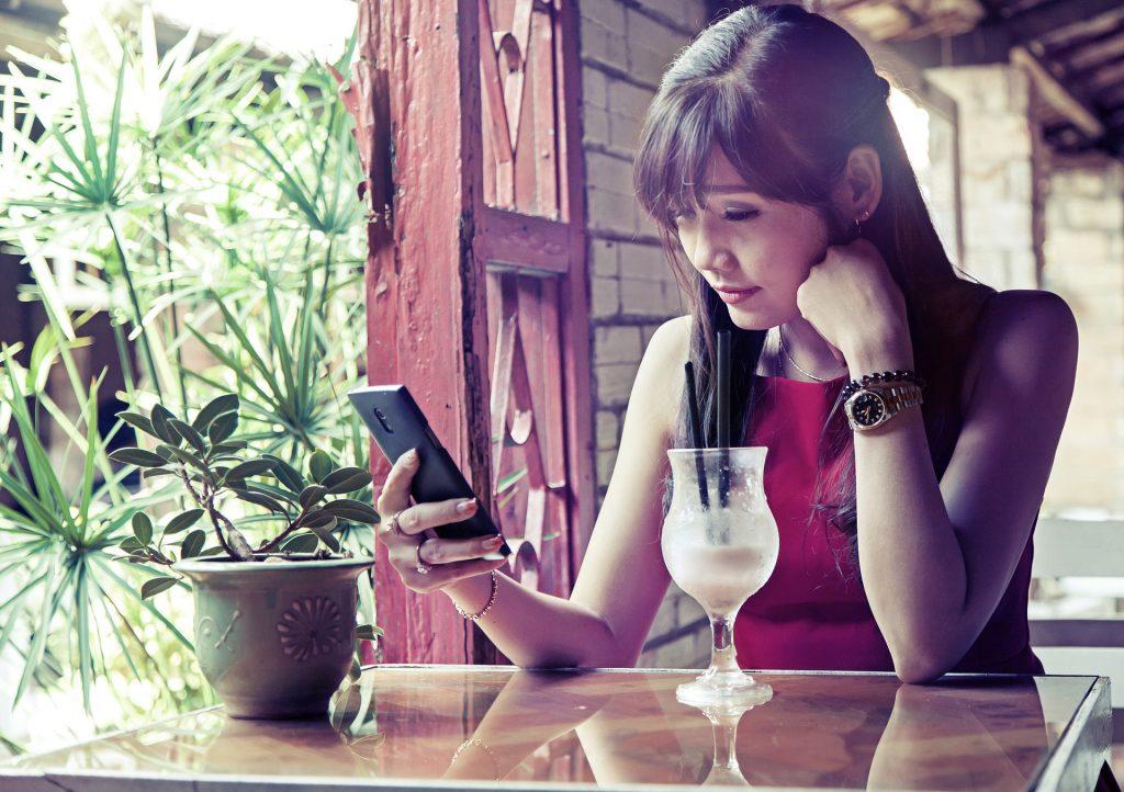 Imagem mostra uma mulher usando a internet do celular no que parece ser um restaurante.