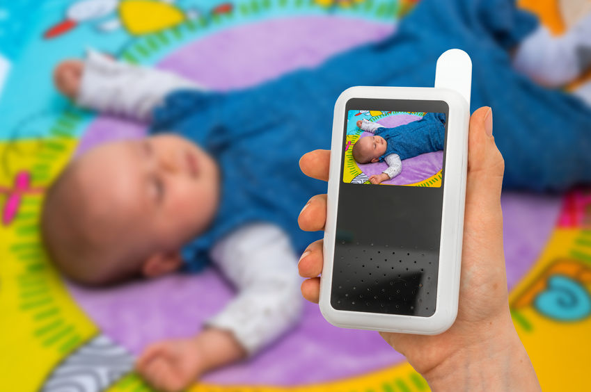 Mão segurando monitor de babá eletrônica com bebê em visor.