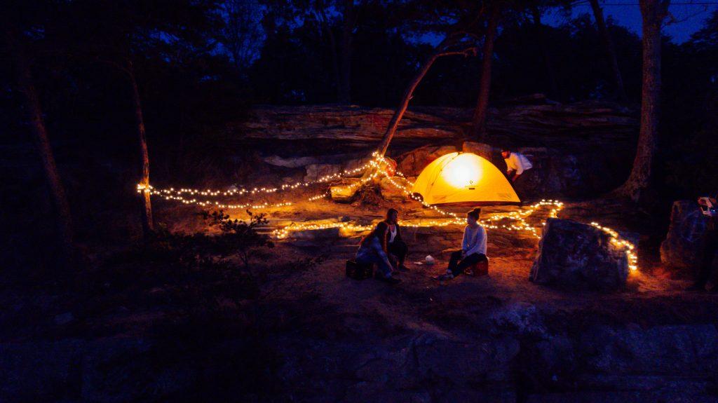 Imagem mostra três mulheres sentadas em semicírculo num acampamento, com uma barraca iluminada atrás, onde há também um homem.