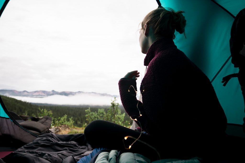 Imagem mostra uma mulher sentada dentro de uma barraca aberta, de costas para câmera, olhando para uma paisagem montanhosa.
